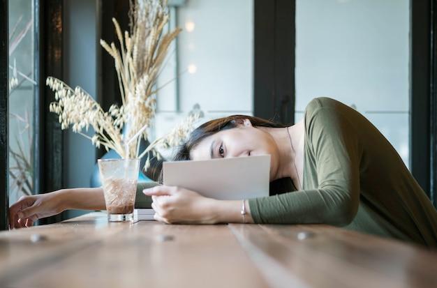 La donna asiatica del primo piano ha mentito per la lettura del libro in caffetteria con il fronte felice