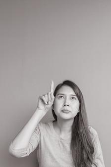 La donna asiatica del primo piano sostiene un punto del dito per spaziare con il fronte noioso