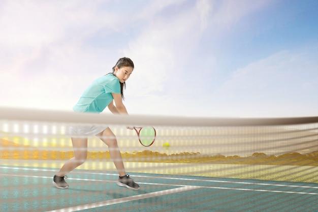 La donna asiatica del tennis con una racchetta di tennis in sue mani ha colpito la palla