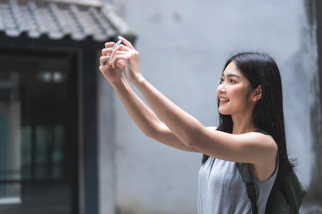 La donna asiatica del viaggiatore che per mezzo del telefono cellulare prende un'immagine mentre passa il viaggio di festa a pechino, cina