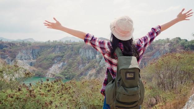 La donna asiatica del viaggiatore con zaino e sacco a pelo della viandante che cammina alla cima della montagna, femminile gode delle sue feste sull'avventura di avventura che ritiene la libertà.