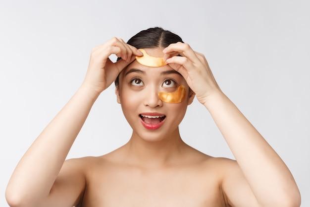 La donna asiatica dell'adolescente di bellezza si preoccupa della sua pelle con le toppe delle maschere di occhio dell'oro sotto gli occhi