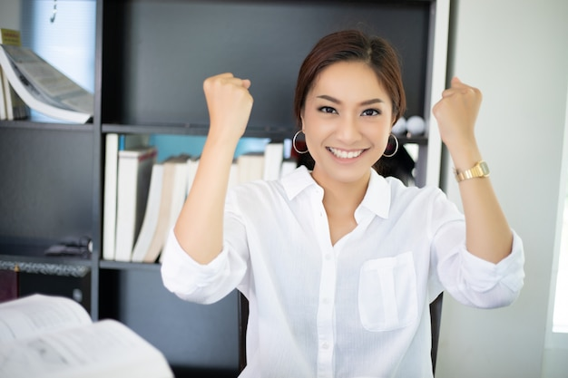 La donna asiatica di affari arma per il successo di celebrazione che funziona, riuscito