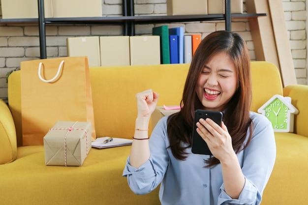 La donna asiatica di affari è soddisfatta del suo ordine in linea in smartphone.