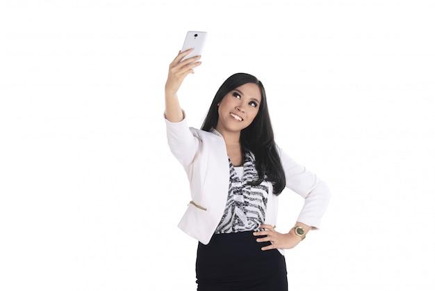 La donna asiatica di affari prende il selfie con il suo smartphone