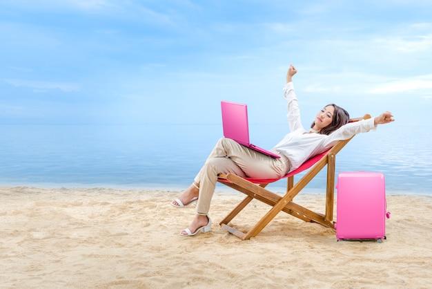 La donna asiatica di affari si rilassa quando lavora con il computer portatile che si siede nella sedia di spiaggia sulla spiaggia