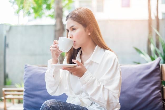 La donna asiatica di affari sta bevendo il caffè di mattina alla caffetteria