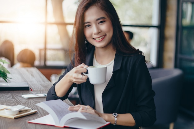 La donna asiatica di affari sta lavorando e sta bevendo il caffè a tempo di rilassamento