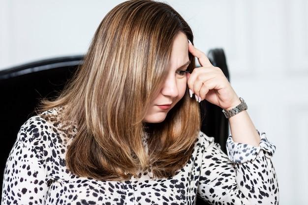 La donna asiatica di affari sta pensando mentre sedendosi su una sedia.