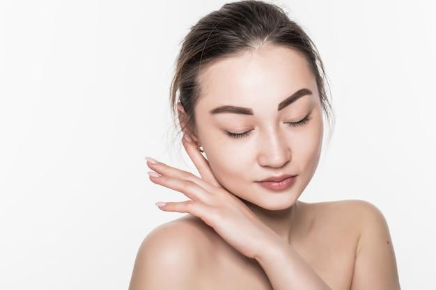 La donna asiatica di bella cura di pelle gode e si rilassa isolata sulla parete bianca.