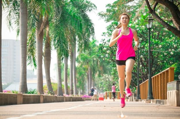 La donna asiatica di sport funziona ed esercita in parco all'aperto