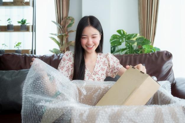La donna asiatica disimballa l'imballaggio dopo lo shopping online dal discount