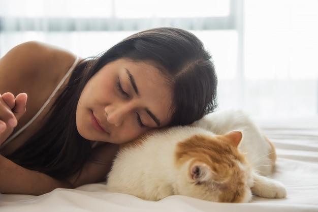 La donna asiatica dorme con il gatto esotico dello shorthair