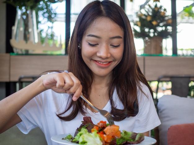 La donna asiatica è felice di mangiare insalata di salmone