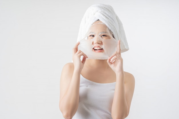La donna asiatica è foglio maschera facciale. lei è felice e sorpresa.
