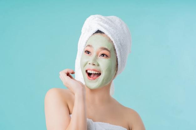 La donna asiatica è maschera facciale. lei è felice e sorpresa.