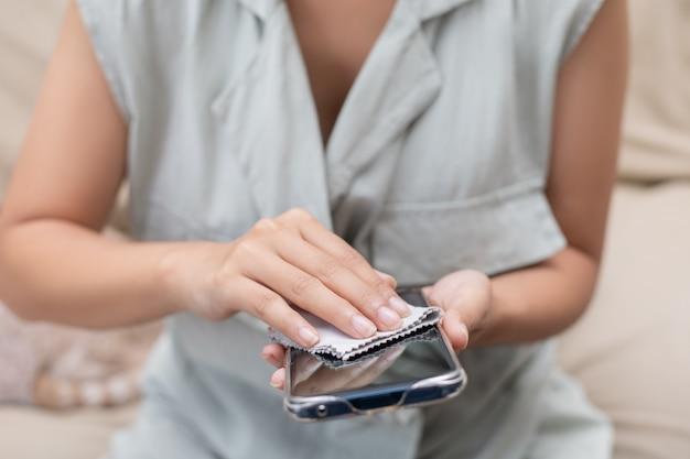 La donna asiatica è seduta, pulendo e pulendo per uccidere i germi su un telefono cellulare.
