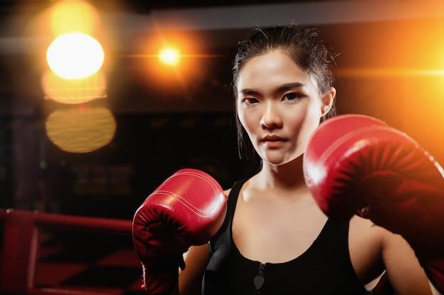 La donna asiatica esamina la macchina fotografica mentre pratica il pugilato in palestra