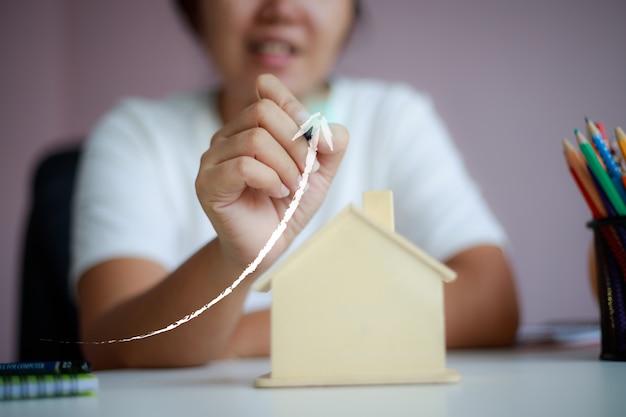 La donna asiatica felice che usando la matita disegna la forma superiore della freccia con la metafora di legno del porcellino salvadanaio della casa che risparmia i soldi per l'acquisto della casa
