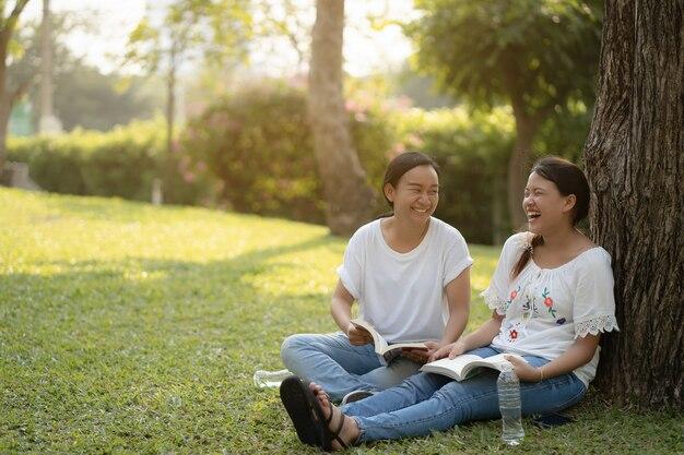 La donna asiatica felice due sta rilassando nel parco