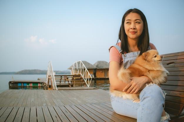 La donna asiatica felice gode di di rilassarsi con il suo cane.