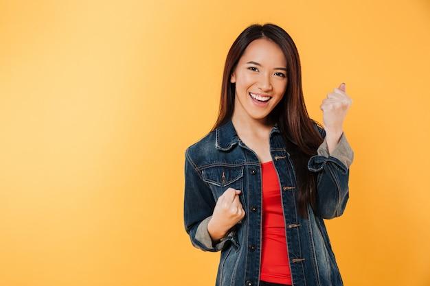 La donna asiatica felice in rivestimento si rallegra e l'esame della macchina fotografica