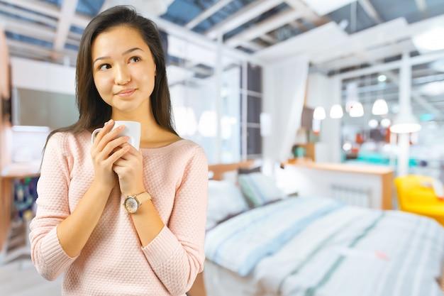 La donna asiatica gode di con una tazza di caffè