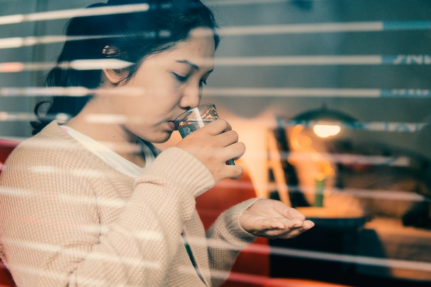 La donna asiatica ha il raffreddore e prende una pillola a casa, concetto di sanità. messa a fuoco selettiva e morbida.
