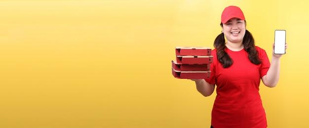 La donna asiatica in spiritello malevolo, dando l'ordine italiano la pizza italiana in scatole di cartone ha isolato il telefono cellulare della tenuta con lo schermo vuoto bianco in bianco.