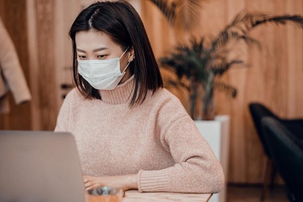 La donna asiatica in una maschera protettiva si siede in un caffè ad un computer portatile. proteggere la popolazione dai coronavirus proteggendo il tratto respiratorio. una ragazza lavora in una caffetteria con una mascherina medica blu
