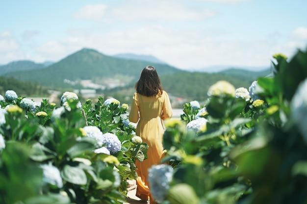 La donna asiatica in vestito giallo cammina nel giardino di fiori dell'ortensia.