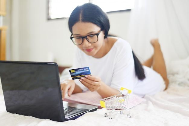 La donna asiatica passa la tenuta della carta di credito e per mezzo del computer portatile per l'acquisto online con il carrello sul letto.