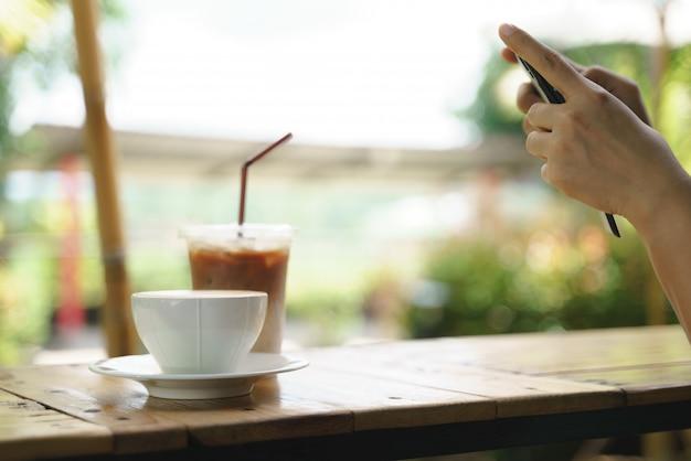 La donna asiatica prende una foto del caffè caldo del latte