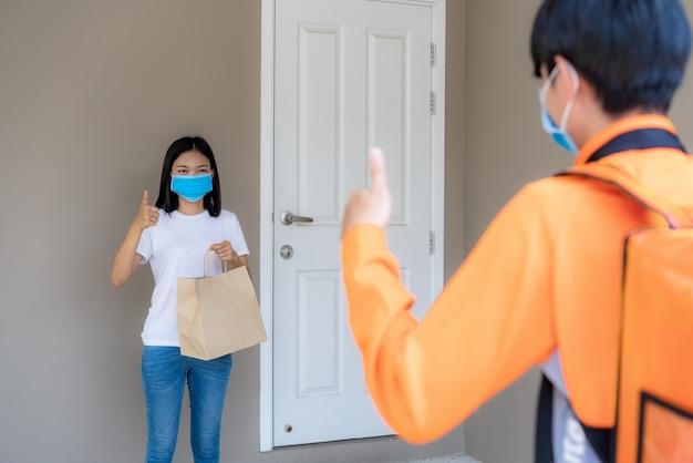 La donna asiatica raccoglie la borsa dell'alimento di consegna dalla maniglia della porta e dal pollice su senza contatto o senza contatto dal cavaliere di consegna con la bicicletta in casa per il distanziamento sociale per il rischio di infezione. concetto di coronavirus