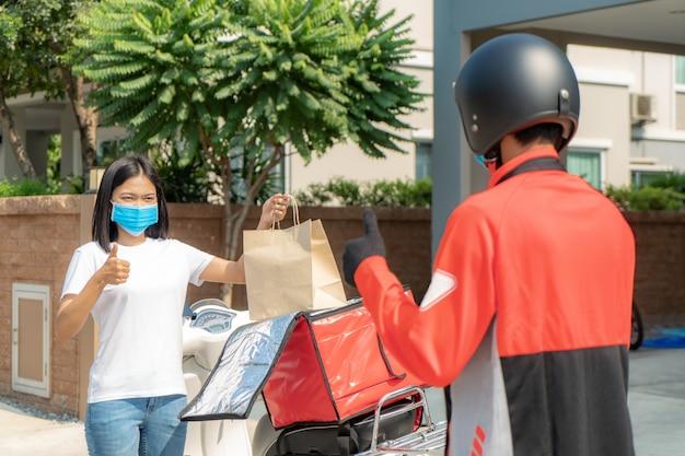 La donna asiatica raccoglie la borsa dell'alimento di consegna dalla scatola e dal pollice in su senza contatto o senza contatto dal cavaliere di consegna con la bicicletta nella casa di fronte per allontanare sociale per il rischio di infezione. concetto di coronavirus