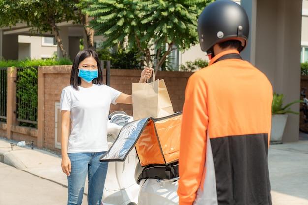 La donna asiatica raccoglie la borsa dell'alimento di consegna dalla scatola per senza contatto o senza contatto dal cavaliere di consegna con la bicicletta nella casa di fronte per il distanziamento sociale per il rischio di infezione.