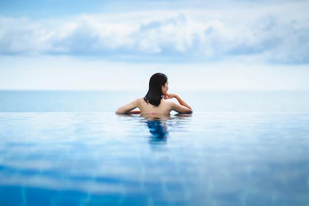 La donna asiatica si distende in stagno sulla spiaggia
