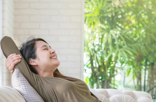 La donna asiatica si distende sul sofà nel suo tempo libero nel fondo della stanza