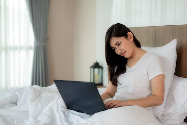 La donna asiatica si rilassa facendo uso del computer portatile e nella camera da letto.