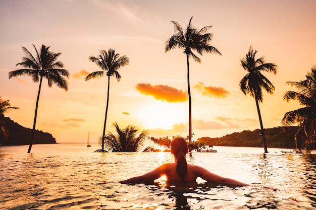 La donna asiatica si rilassa in stagno sulla spiaggia