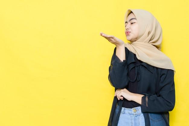 La donna asiatica soffia le palme con spazio vuoto.