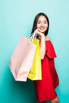 La donna asiatica sta acquistando di estate con i sacchetti della spesa gode di di comperare.