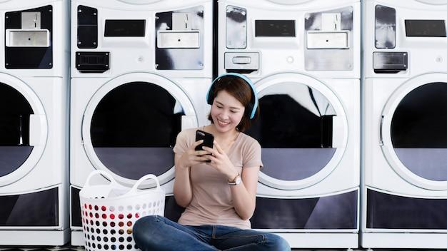La donna asiatica sta ascoltando musica al negozio di lavanderia