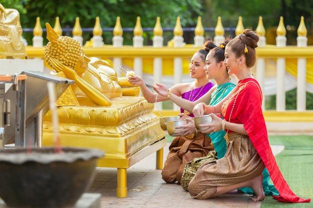 La donna asiatica sta bagnando felicemente la statua di buddha in tailandia.