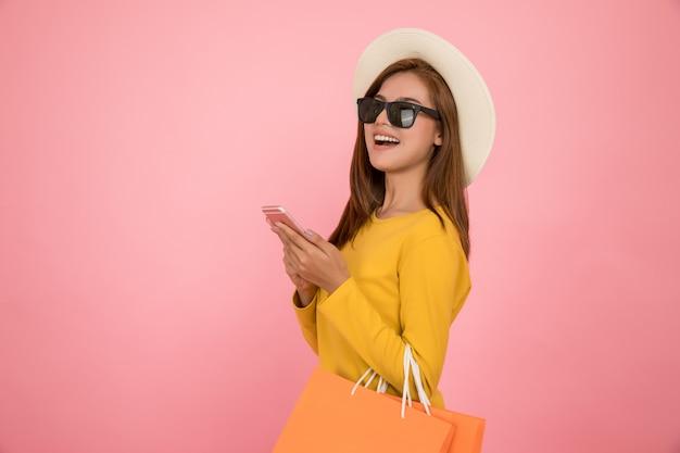 La donna asiatica sta comperando nel vestito giallo dai vestiti casuali dell'estate