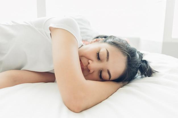 La donna asiatica sta dormendo sul suo letto accogliente bianco.