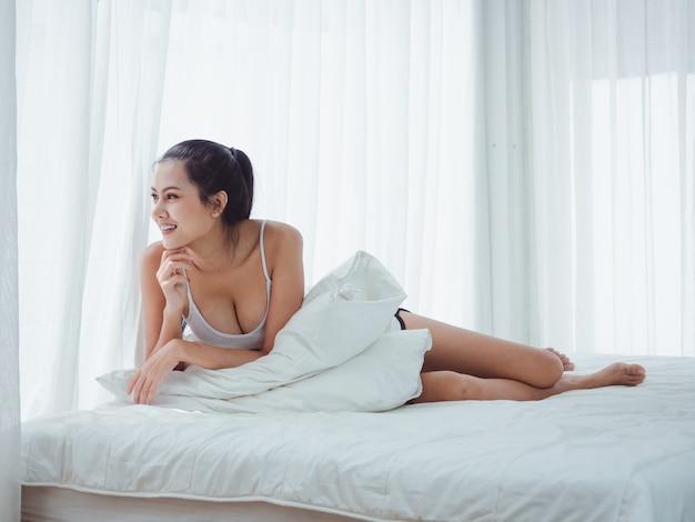 La donna asiatica sta guardando fuori dalla finestra