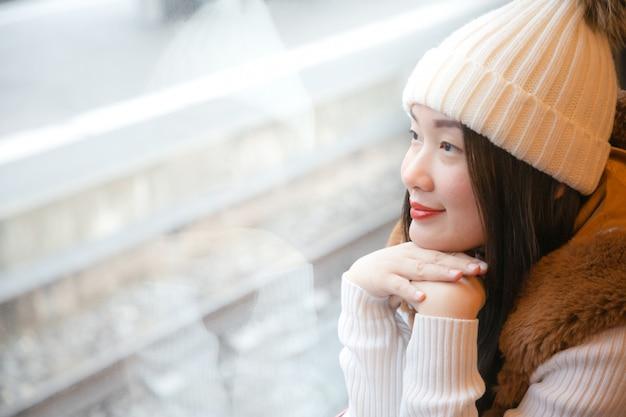 La donna asiatica sta guardando la vista naturale dalla finestra sul treno