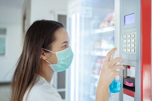 La donna asiatica sta iniettando alcol per uccidere i germi sul pulsante dei distributori automatici di bevande