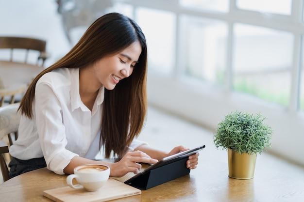 La donna asiatica sta usando la compressa con la faccia sorridente